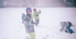 A group of children have a snowball fight in a storm at school