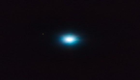 O exoplaneta, intitulado CVSO 30c, é o ponto marrom na parte esquerda da foto. A mancha brilhante central é sua estrela mãe.