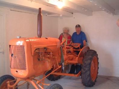 Torleiv og Mari i rommet de har pusset opp og med traktoren som skal være et trekkplaster i museet.
