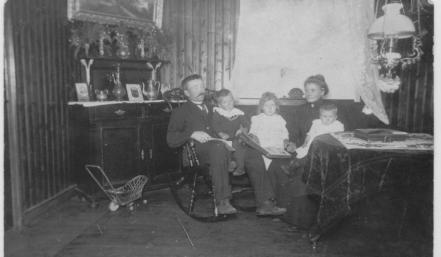 Interiør i et vanlig hjem fra første del av 1900. (Familien er Bernt J.S.Ilebekk, på fanget hans: Sverre B. Ilebekk, Agnes Ilebekk, Emma Ilebekk og på fanget hennes Inger Ilebekk)