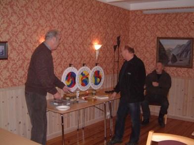 """Kjell Koland og Olav Bårdsen og Helge Skuland forbereder gevinstbordet. Merk den flotte """"trekkemaskinen"""" som Per Slettedal har laget."""