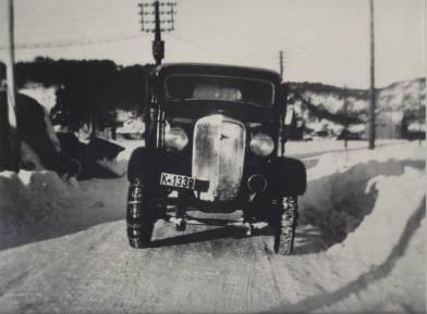 En førkrigsmodell av lastebil som tilhørte Kristian Iglebæk. Legg merke til at den har bare kjetting på det høyre forhjulet. Det var vanlig at en brukte det som styrekjetting. Den gang var det ikke krav om at hjul på samme aksel skulle ha samme utrustning. En kan også skimte brøyteploger til venstre i bildet og denne bilen har sikkert vært nyttet til brøyting.