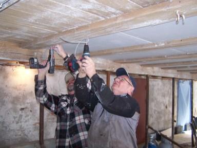 Ole Trygve Almedal og Odd Erling Aurebekk skrur fast gipsplater i taket.