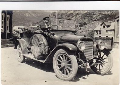 Sjåføren på denne staselige bilen er Theodor L. Ilebekk. Han tok sertifikatet svært tidlig og på dette bildet er han sjåfør for en handelsreisende i firmaet Andresen og Myrstad i Kristiansand. Det var ikke så mange som hadde sertifikat, og mange firmaer ansatte egen sjåfør for å kjøre selgeren rundt til de ulike kundene. (Theodor overtok sammen med sin bror Alfred ,Øvrebøruta, men fikk poliomyelitt, og de solgte derfor videre til Kristian Iglebæk og sønnene hans Arthur og Olav.)