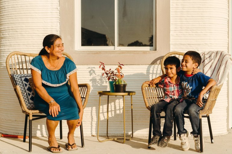 a-family-sits-on-the-patio-outside-their-finished-home