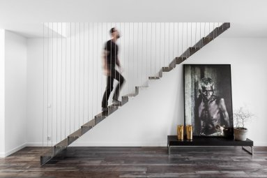 metal-stairs-attached-via-wires-allow-an-abundance-of-light-to-reach-the-first-floor