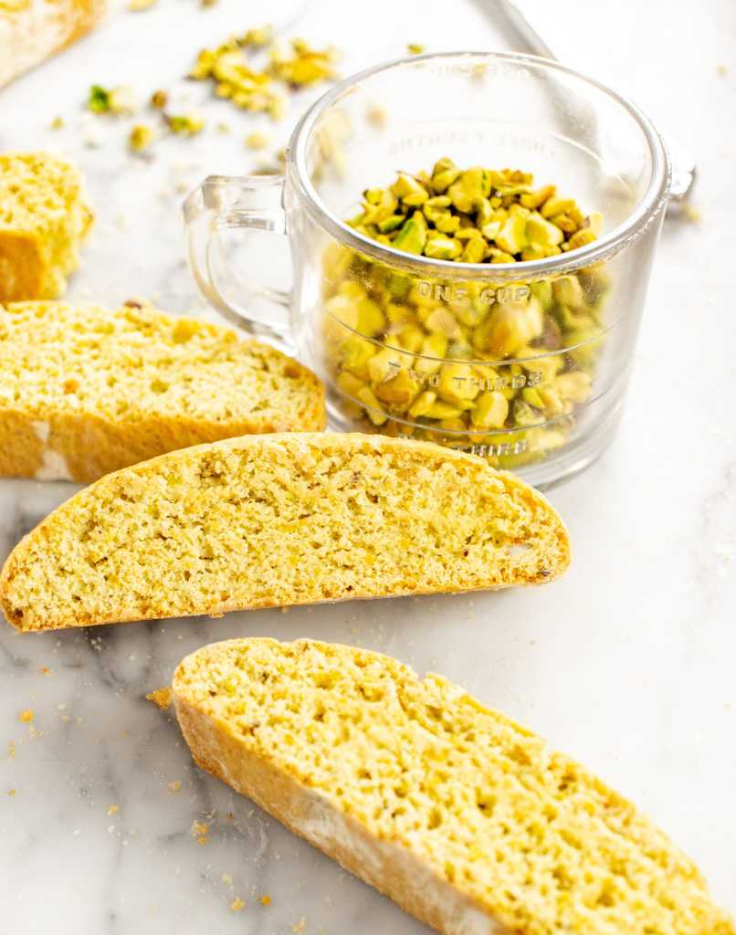 Pistachio biscotti with a cup of pistachios