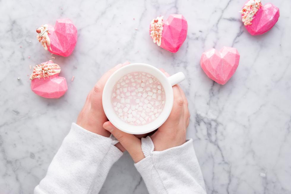 hands holding a mug of pink hot chocolate