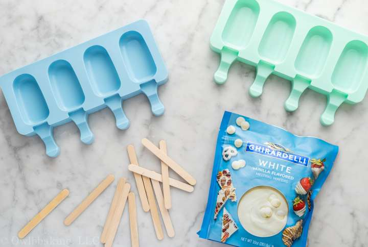 Cakesicle molds, popsicle sticks and candy melts on marble