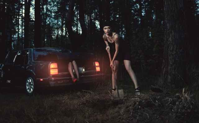 woman in black tank top and black shorts standing beside red car
