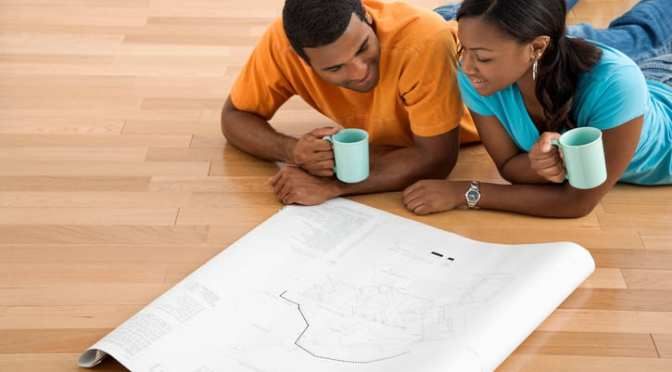 African American male and female couple lying on floor looking at architectural blueprints for their ADU