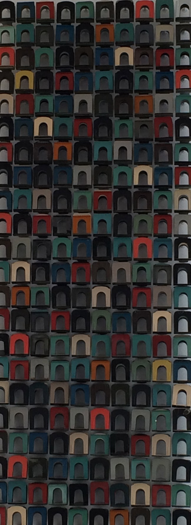 A surprisingly charming work of art hanging in a stairwell, created with colorful old bookends