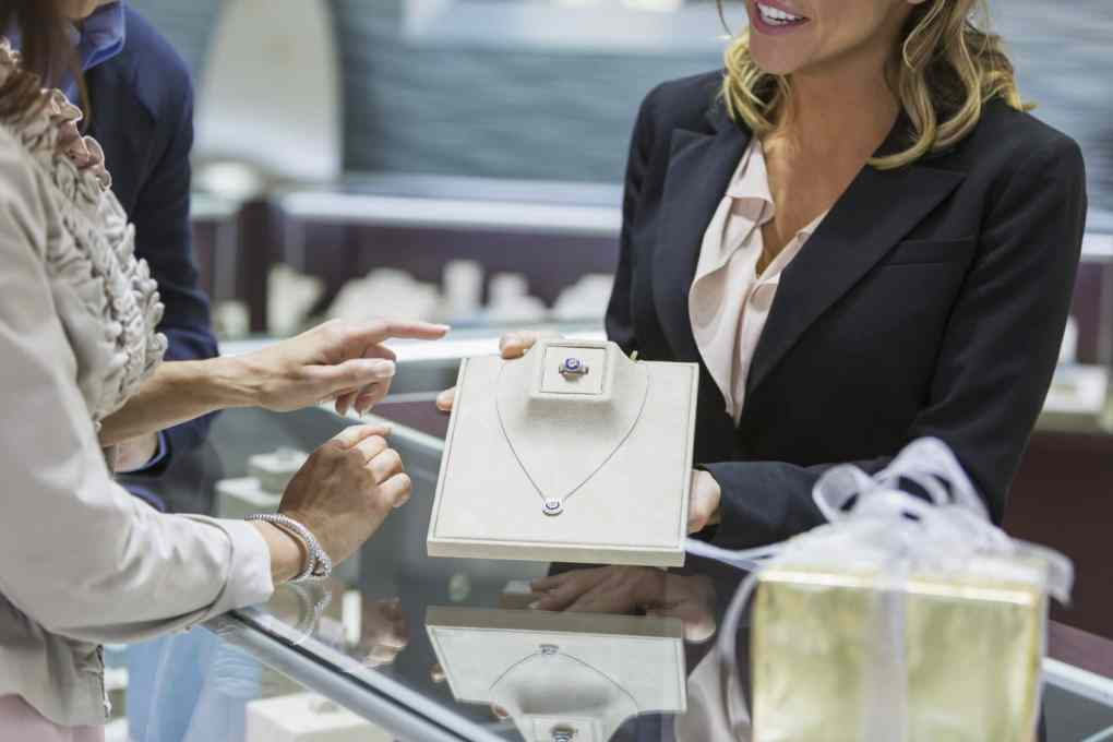 Cropped view of a saleswoman in a jewelry store helping a couple and showing the female customer a ring and necklace from the display case.