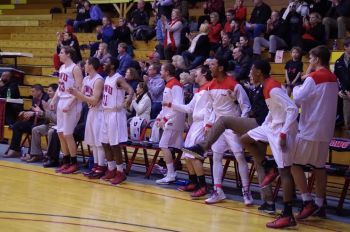 The team reacts to junior post Claude Gray's fast break score. Photo courtesy of Spenser Hickey.