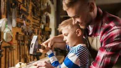 Мужчина с сыном забивают гвоздь