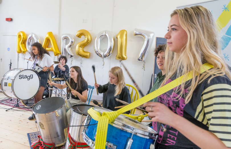 Teenage girls performing on the drums