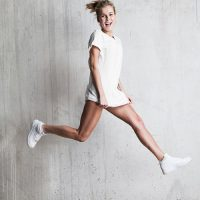 athletic girl dressed in a white T-shirt jumps