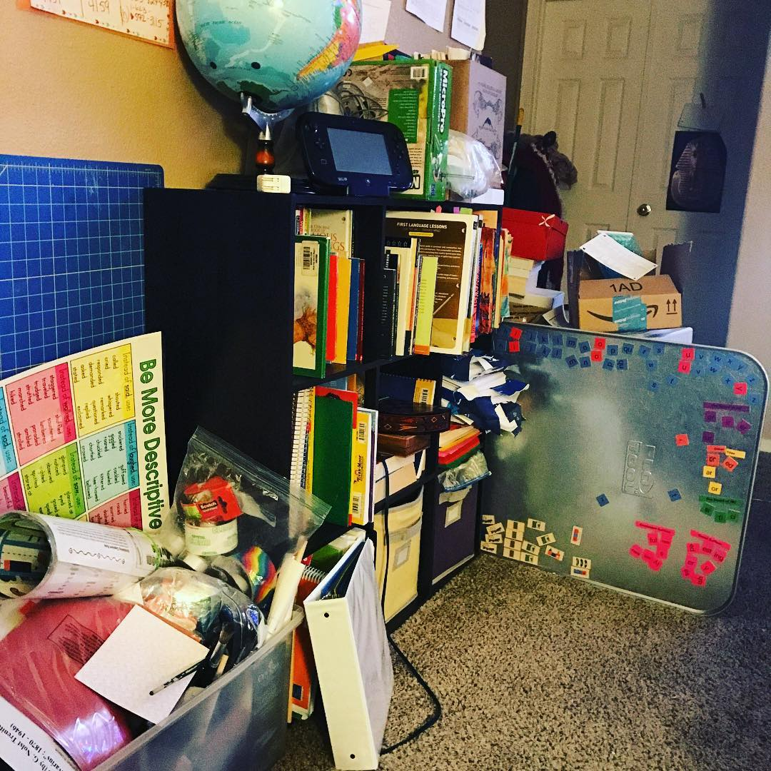 Bookshelves and boxes filles with fith grade homeschooling books and curriculum