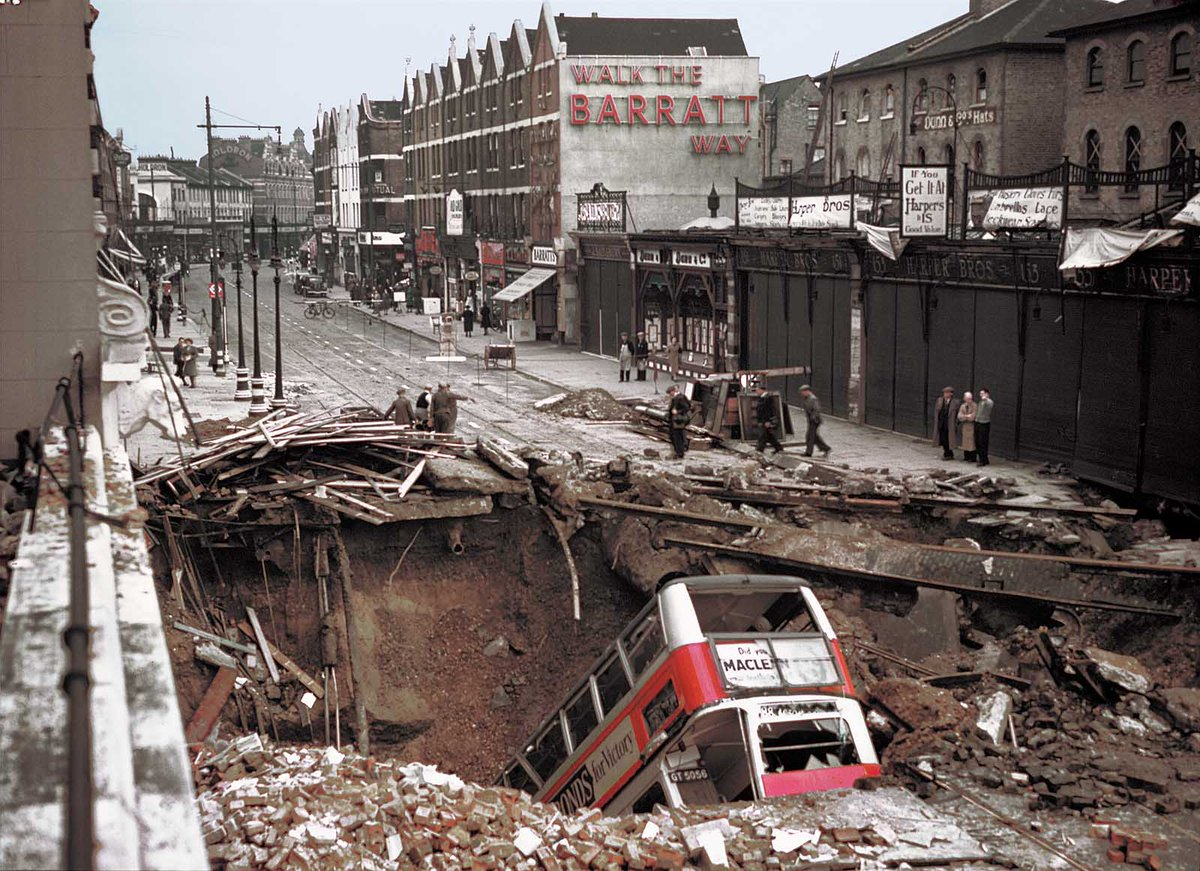 A London bus has plunged headlong into the huge bomb crater outside Balham Tube Station- in dark of the nightly blackout, bus driver didn't see it.The bus is being removed from the Balham Underground station bomb crater with a crane- amazingly, no passengers were seriously hurt by the crash