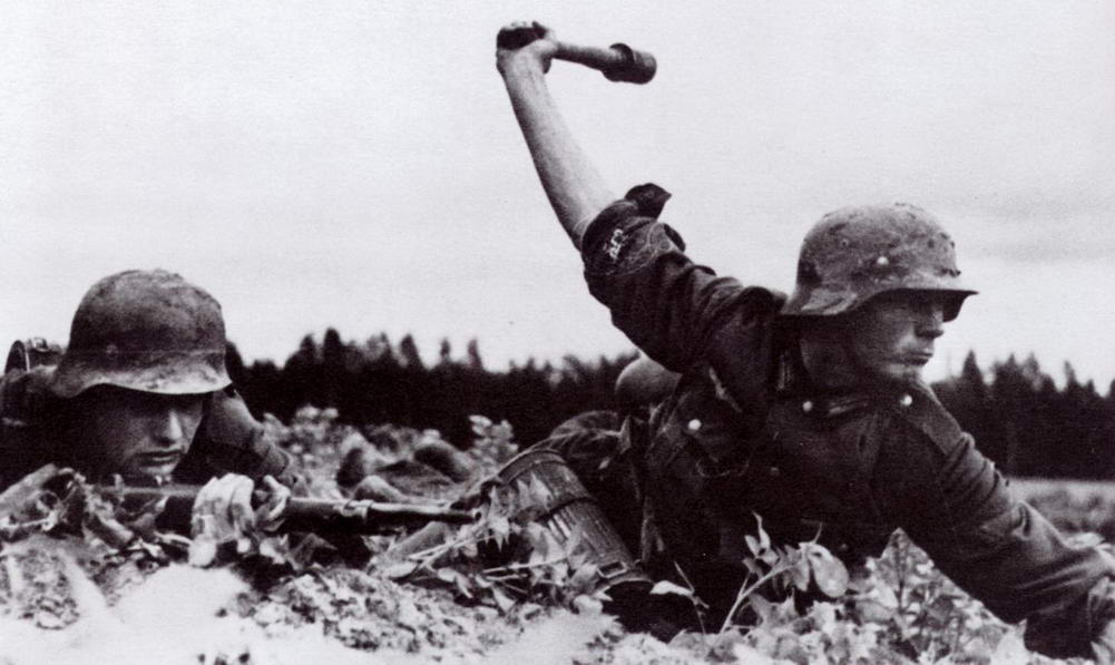German Soldier Throws Stick Grenade. Deutsche Heer Obergefreiter (German Army Senior Lance-Corporal) prepares to throw a Model 24 Stielhandgranate (Stick Hand Grenade) ww2