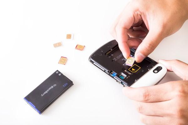 SIMカードをスマホに挿入するところ
