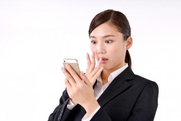スマホのバッテリー消費が激しすぎて驚く、スーツ姿の女性