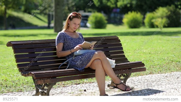 Young Woman Reading Book And Sitting Bench