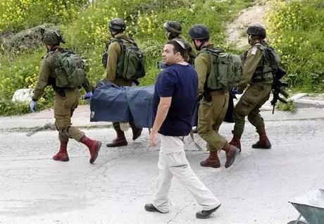 Soldados de Israel recolhem corpos de palestinos mortos por disparos após esfaquear um militar israelense na Cisjordânia.