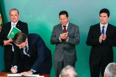 Presidente Jair Bolsonaro assina o decreto da posse de armas no Brasil sob os olhares do ministro da casa civil, Onyx Lorenzoni, do vice presidente Hamilton Mourão e do ministro da Justiça e Segurança Pública, Sergio Moro