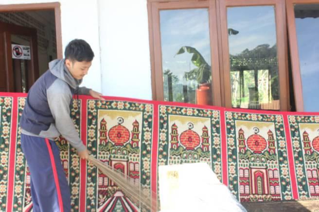 kang Arie membersihkan karpet di luar