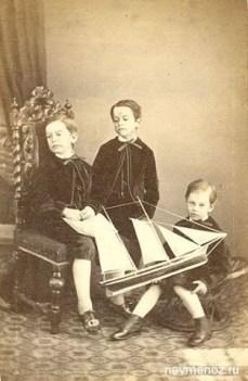 Tre gutter med seilbåt