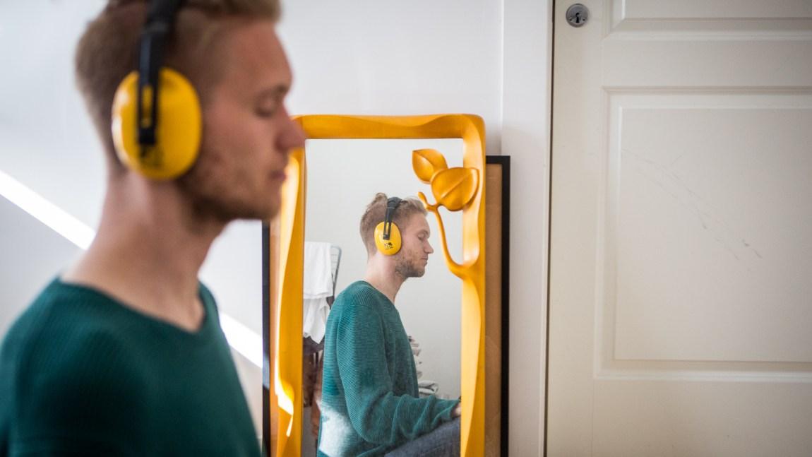 Hørselvern er noe Andreas (26) bruker for å dempe verden til et håndterbart nivå. Andreas har ME – det som på folkemunne ofte kalles kronisk utmattelsessyndrom. (Foto: Tom Øverlie, NRK)