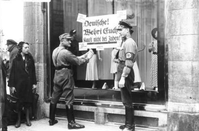 """Nazister henger plakater i vinduene på jødisk eide butikker hvor det står """"Ikke kjøp fra jødene""""."""