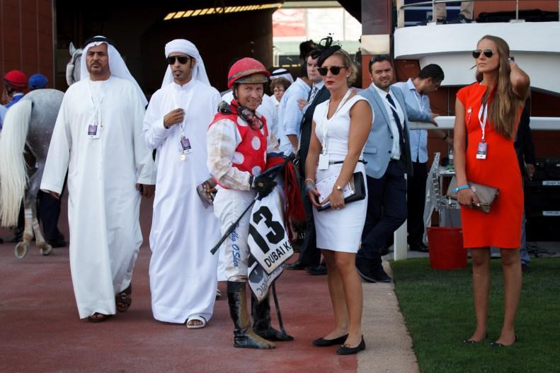 Veronika Aske fra (28) Larvik (i hvit kjole) hadde med tre av araberhestene hun trener for sjeiken av Abu Dhabi i det første løpet. Det holdt dessverre ikke. (Foto: Matias Nordahl Carlsen, NRK)