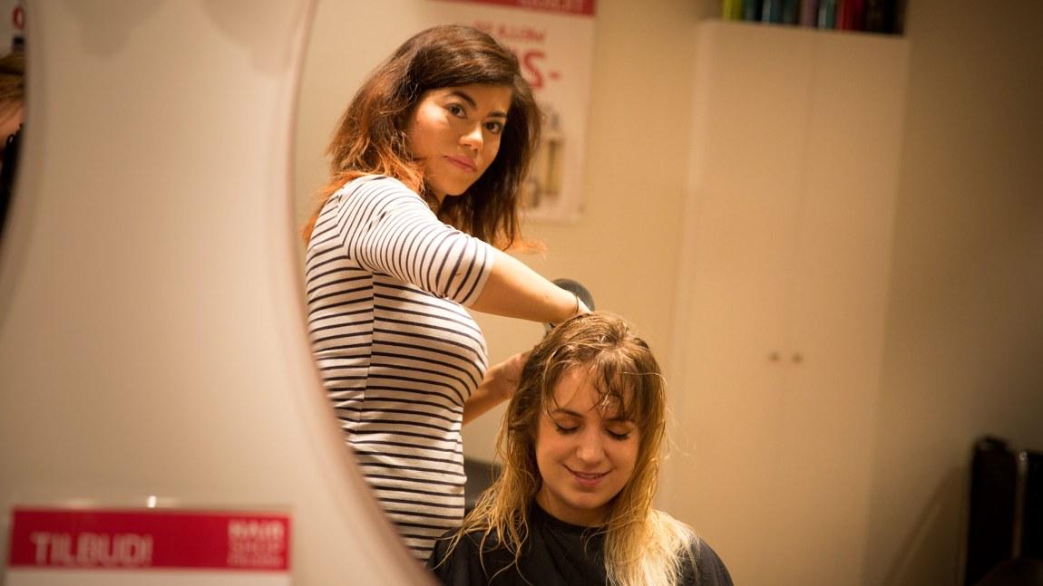 Hanne Villegas (26) friserer Lacie Goff (23). De to har blitt godt kjent. Hanne sier at de fleste kundene er artige og trivelige, men noen deler litt for mye fra privatlivet. (Foto: Mari Aftret Mørtvedt/NRK)