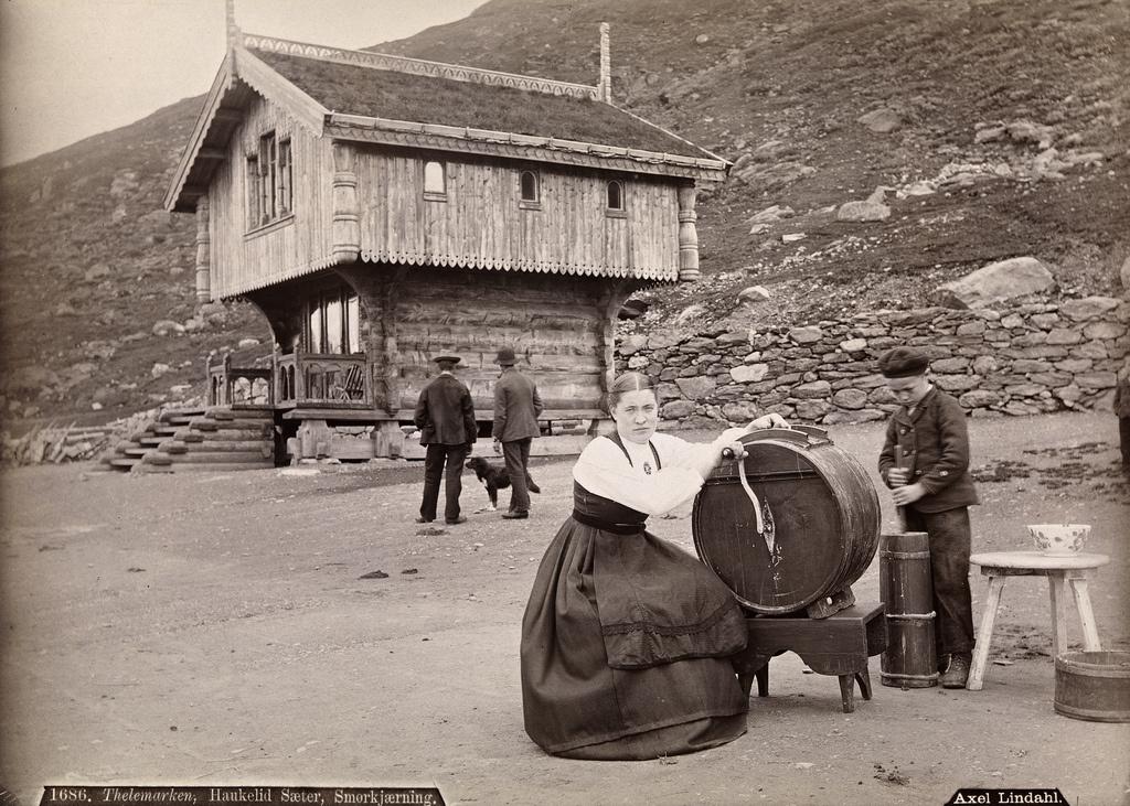 Budeie på Haukeliseter demonstrerer kinning av smør for omreisende fotograf trolig på 1880-tallet. (Foto: Axel Lindahl)