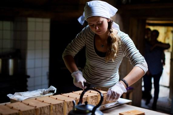 Camilla Vanessa Askeland (23) skjærer opp den første brunosten hun har laget selv. Den har fått navnet Berta, etter bestemoren hennes. Foto: Wanda Nathalie Nordstrøm