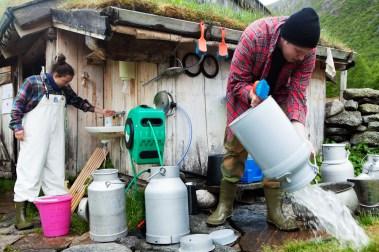 Det er strenge krav til renslighet når en driver med matproduksjon- og salg. Simen Flaten Svisdal (19) vasker melkespann i base og syre. (Foto: Wanda Nathalie Nordstrøm)