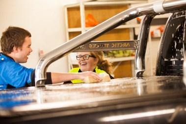 """Silje Fridjofsen (19) og de andre lærer å jobbe gjennom linja """"arbeid i praksis"""". Her vasker de biler utvendig og innvendig. (Foto: Lars Haugdal Andersen/NRK)"""