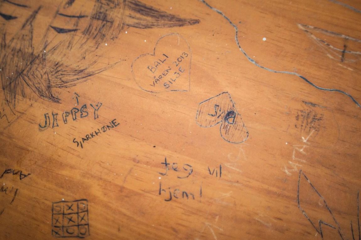 «Jeg vil hjem». Skriblerier på en av skolepultene. (Foto: Andrea A. Thiis-Evensen)