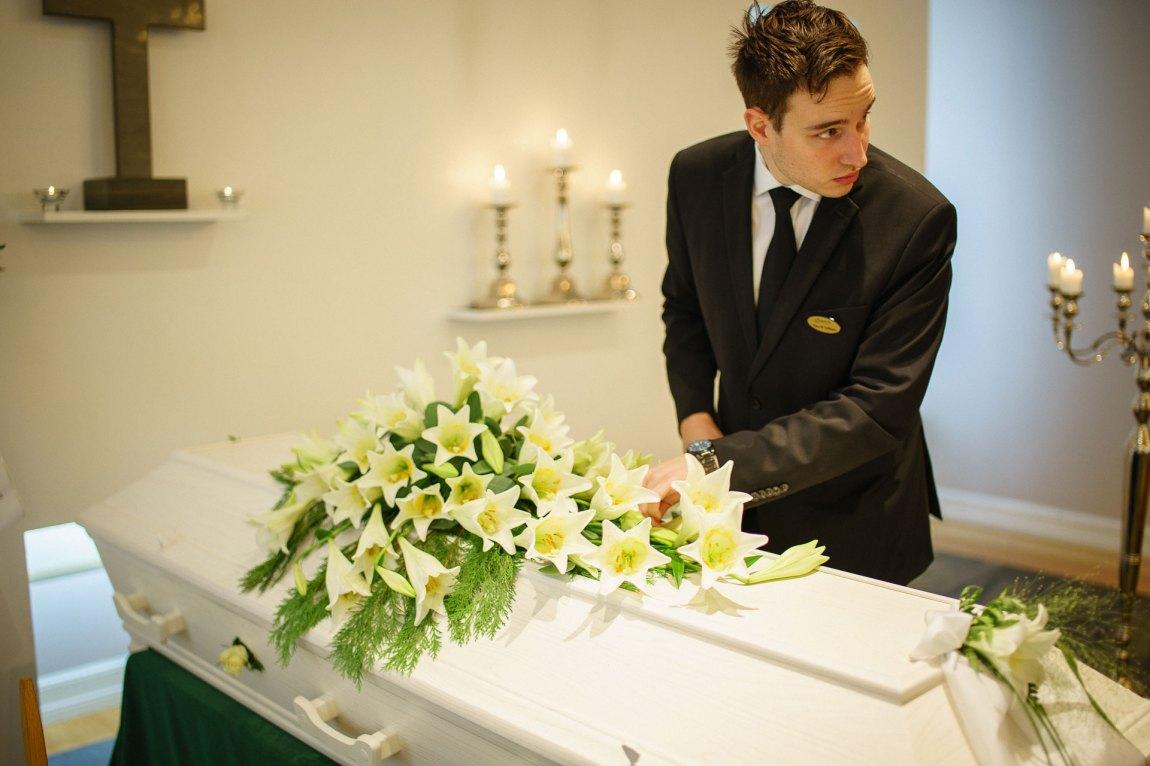 Hans Magnus danderer blomstene på kista før bisettelsen.