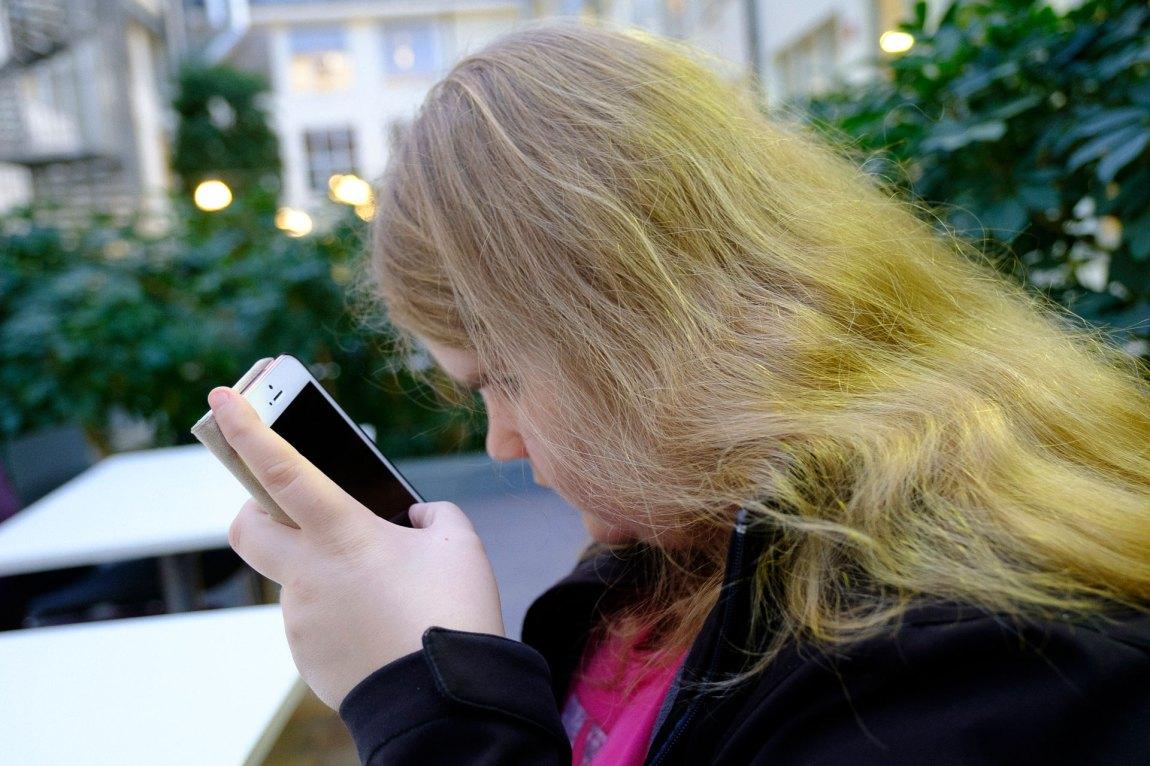 Lena tastar inn ei melding på mobiltelefonen. Ho har på seg rosa t-skjorte og svart jakke. Ho har stort krusete gult hår som fell nedover skuldrene. I bakgrunnen er det planter. Lena har skrudd av skjermen på iPhonen for å spare batteri. Ho navigerer med swipes og talestyring. Foto: Lars Erik H. Andreassen