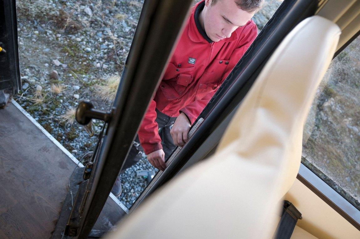 Markus måler opp avstand på ei bussdør. Han føler seg fram på linjalen for å finne rett lengde. Blindeskrift på metermålet gjer at Markus får nøyaktige mål utan å sjå. Foto: Lars Erik H. Andreassen