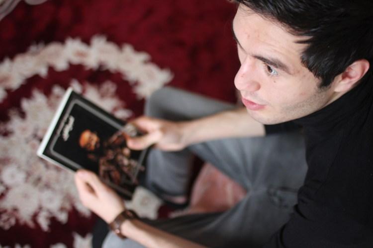 Majid elsker realfag og å lese. Her sitter han med en bok av den polske journalisten Ryszard Kapuściński. Foto: Frid K. Hansen