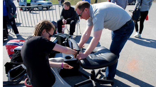 """Martin Flåten får hjelp av far til å skru opp kontorstolen. """"Du får litt følelsen av å flytte inn, Vikingskipet er på en måte mitt andre hjem. Drømmehjemmet!"""" (Foto: Silje Strømmen, NRK P3)"""