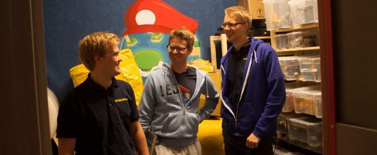 Petter Halle (fra venstre), Aleksander Waage og Audun Wilhelmsen er i lageret for å hente flere konsoller. (Foto: Remi Horgar).