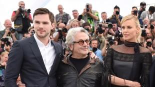 Skuespillerne Nicholas Hoult og Charlize Theron med regissør George Miller mellom seg i Cannes (AFP PHOTO / ANNE-CHRISTINE POUJOULAT)-