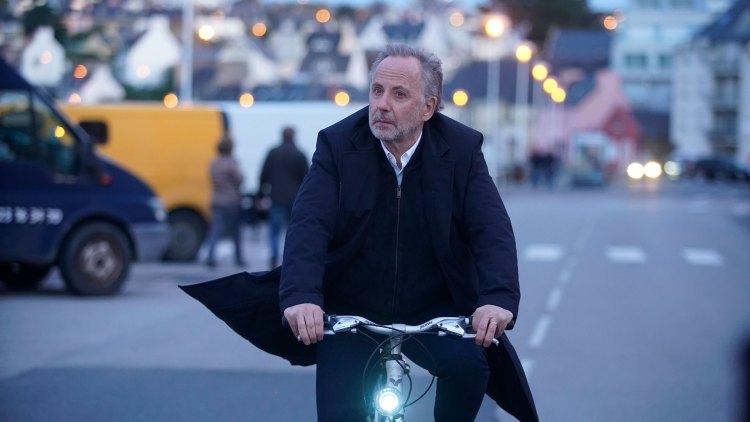 Alvorlig mann på sykkel med flagrende frakk