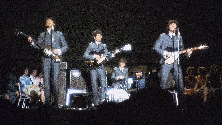 John Lennon (t.h.) på scenen med resten av The Beatles i 1964. Foto: NTB Scanpix / AP Photo.