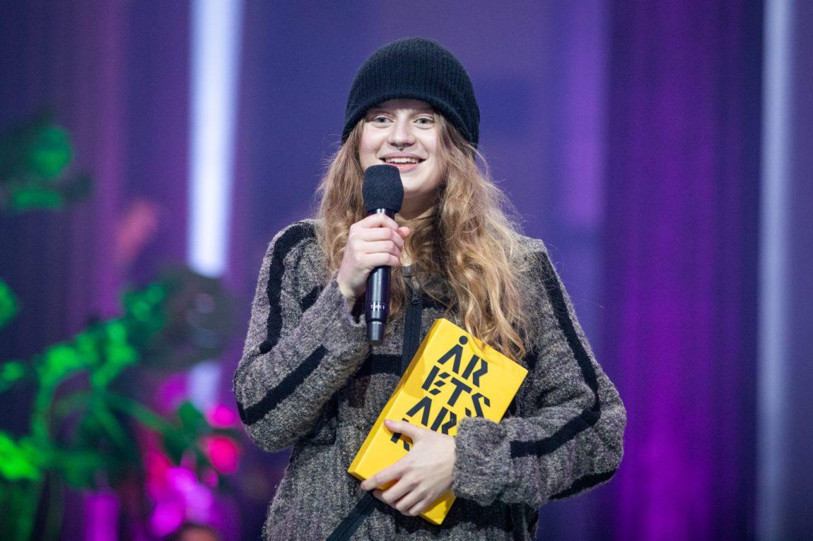 Marie står på secenen iført en stor hettegenser, svart lue, mikrofon i den ene hånden og prisen i den andre